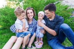 Подборщики гриба Счастливая семья с корзиной грибов сидит на зеленой лужайке Стоковое фото RF