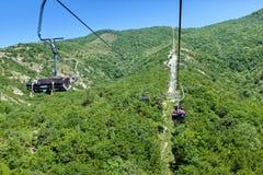 Подвесной подъемник идя вверх гора Красивый заход солнца на горах вполне деревьев, апельсина, зеленого цвета и сини за подвесным  Стоковое Фото