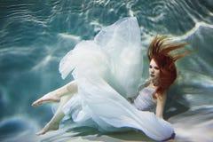 Подводная девушка Красивая рыжеволосая женщина в белом платье, плавая под водой стоковые фотографии rf