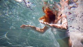 Подводная девушка Красивая рыжеволосая женщина в белом платье, плавая под водой стоковое изображение rf
