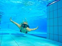 Подводное изображение: заплывание женщины с маской и голубым бикини в бассейне стоковое фото