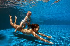 Подводное изображение mam и девушки стоковая фотография rf