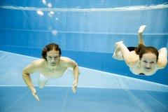 Подводный взгляд молодого заплывания пар в бассейне Стоковые Фотографии RF