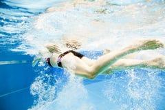 Подводный взгляд молодого заплывания пар в бассейне Стоковое Фото