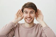 Подготавливайте для того чтобы слушать самые последние сплетни Портрет красивого excited европейского человека держа ладони прибл Стоковое Изображение