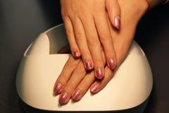 подготавливайте шеллак маникюра покрасьте золото шеллака розовое стоковое фото rf