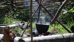 Подготавливать еду в баке над огнем видеоматериал