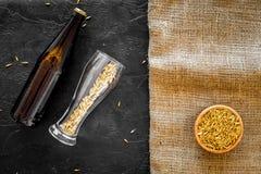 Подготавливать пиво Ячмень около пивной бутылки и стекла на модель-макете взгляд сверху предпосылки черноты и холста Стоковое Изображение RF