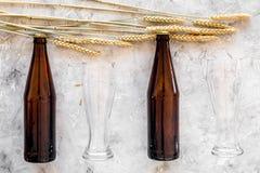 Подготавливать пиво Ячмень около пивной бутылки и стекла на сером взгляд сверху предпосылки Стоковое фото RF