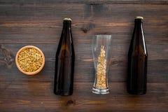 Подготавливать пиво Ячмень около пивной бутылки и стекла на деревянном взгляд сверху предпосылки Стоковые Фото