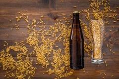 Подготавливать пиво Ячмень около пивной бутылки и стекла на деревянном взгляд сверху предпосылки Стоковое Изображение