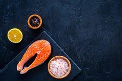 Подготавливать salmon стейк Часть красных рыб на разделочной доске около соли моря, перца, кусков лимона на черной предпосылке по Стоковые Изображения