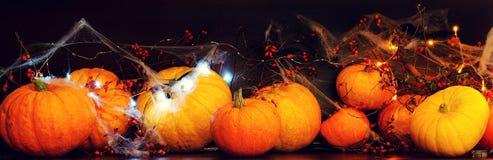 Подготавливающ для хеллоуина, чистки и высекать сторон от тыкв, тыкв на темной таблице с паутинами и bokeh  стоковое изображение rf