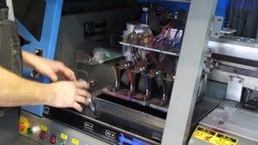 Подготовка для печатного станка больш-формата струйного Мужской работник рук сливает старую краску и обтирает поверхность  акции видеоматериалы