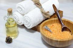 Подготовка для процедуры по курорта - оранжевая соль для принятия ванны в деревянных шаре и ложке, 3 белых полотенцах на деревянн Стоковые Фото