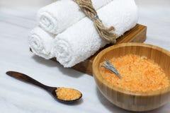 Подготовка для процедуры по курорта - оранжевая соль для принятия ванны в деревянных шаре и ложке и 3 белых полотенцах на деревян Стоковое Изображение RF