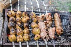 Подготовка мяса с кудрявыми коркой и картошками на гриле стоковые изображения