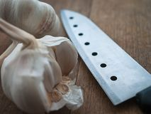 Подготовка натуральных продуктов, варя концепцию: сырцовые головы шариков чеснока, нож на деревенской предпосылке деревянного сто Стоковое фото RF