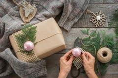 Подготовка на праздник рождества Натюрморт рождества giftbox, оформления, шпагата, ели, хворостин Женщина подготавливает подарок  Стоковое фото RF