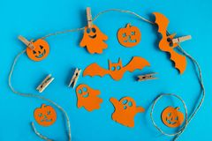 Подготовка на хеллоуин Оранжевые бумажные украшения - призраки, тыквы и летучие мыши на веревочке с штырями на голубой предпосылк стоковые фотографии rf