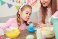Подготовка пасхи матери и дочери совместно дома в ушах зайчика сидя яичка расцветки будет матерью уча дочери Стоковые Изображения RF