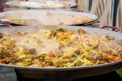 Подготовка паэлья в больших сковородах стоя в ряд Испаряются овощи, специи и мясо цыпленка в больших лотках к prepa Стоковые Изображения