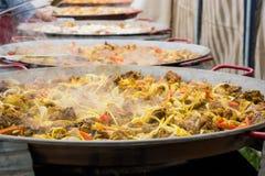 Подготовка паэлья в больших сковородах стоя в ряд Испаряются овощи, специи и мясо цыпленка в больших лотках к prepa Стоковое Изображение