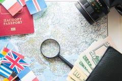Подготовка перемещения: компас, деньги в бумажнике, пасспорте, дорожной карте, лупе, камере, национальных флагах Стоковое фото RF