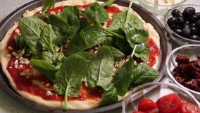 Подготовка пиццы toping Класть свежие листья spinache на отбензинивание пиццы акции видеоматериалы