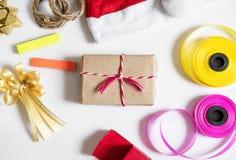 Подготовка подарков рождества на белой таблице Подарочная коробка с красной шляпой santa, подарочная коробка и красочная лента Стоковое Изображение RF