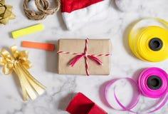 Подготовка подарков рождества на белом мраморном камне Подарочная коробка с красной шляпой santa, подарочная коробка и красочная  Стоковые Изображения RF