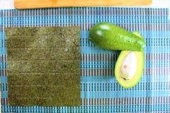 Подготовка суш в кухне, отрезок авокадоа свежих ингридиентов зеленый в половине с морской водорослью и белизна сварили рис на дер бесплатная иллюстрация