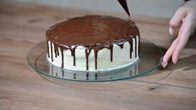 Подготовка торта праздника Девушка льет жидкостный шоколад акции видеоматериалы