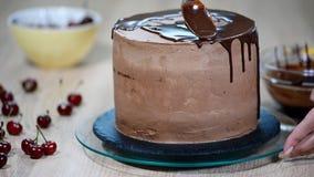 Подготовка торта праздника Девушка льет жидкостный шоколад сток-видео