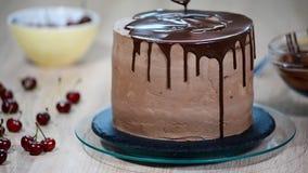 Подготовка торта праздника Девушка льет жидкостный шоколад видеоматериал