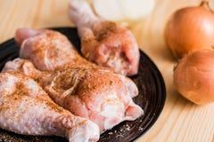 Подготовка цыпленка берца, ноги цыпленка на черной плите, деревянная предпосылка, специи и соль Стоковые Изображения