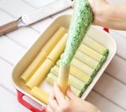Подготовка cannelloni шпината и сыра: Заполнять cannelloni с завалкой шпината и сыра Стоковая Фотография RF