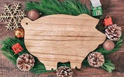 Подготовки рождества, разделочная доска в форме свиней, ветви ели, конусы и украшения стоковые изображения