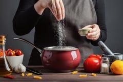 Подготовки спагетти шеф-повара и макаронные изделия, соленая вода, против темной предпосылки, концепция варить Соленая вода женщи стоковые фото