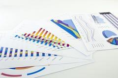 Подготовлять рапорт Голубые диаграммы и диаграммы Бизнес-отчеты и куча документов на серой предпосылке отражения стоковая фотография