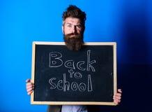 Подготовьте на новый учебный год Учитель рекламирует назад к изучать, начинает учебный год Стойки человека учителя бородатые и стоковое изображение