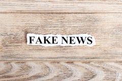 ПОДДЕЛЬНАЯ новость на бумаге НОВОСТИ слова ПОДДЕЛЬНЫЕ на сорванной бумаге текст остальных изображения figurine принципиальной схе Стоковое Изображение
