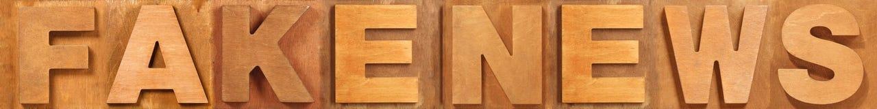 Поддельные слова новостей сделанные старых деревянных писем Стоковые Фотографии RF