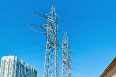 Поддерживает высоковольтную линию электропередач против ясного голубого неба Стоковое Изображение