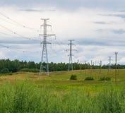 Поддерживает высоковольтные линии электропередач против голубого неба с облаками электрическая индустрия стоковые изображения