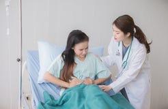 Поддержка доктора к ее женщинам пациентов азиатским с болью в животе в больнице, концепцией здравоохранения стоковое изображение rf
