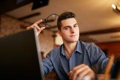 Подлинный портрет молодого уверенно бизнесмена смотря камеру с компьтер-книжкой в офисе Битник с в стеклами и Стоковые Изображения