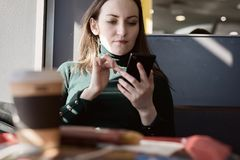 Подлинный портрет молодой женщины сидя в кафе и беседуя на социальных сетях через smartphone, с кофе на таблице внутри Стоковые Фото