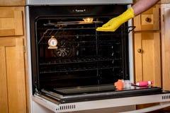 Поднимающ печь положите на полку из прибора с желтой перчаткой Стоковое Фото