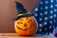 Поднимите голову домкратом фонарика высекаенную от тыквы хеллоуина, деревянной предпосылки, флага США стоковые фотографии rf